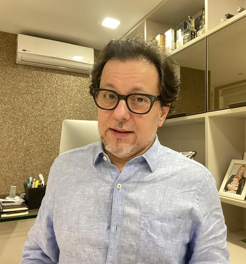 Homem de negócios com camisa azul e óculos de aro preto.