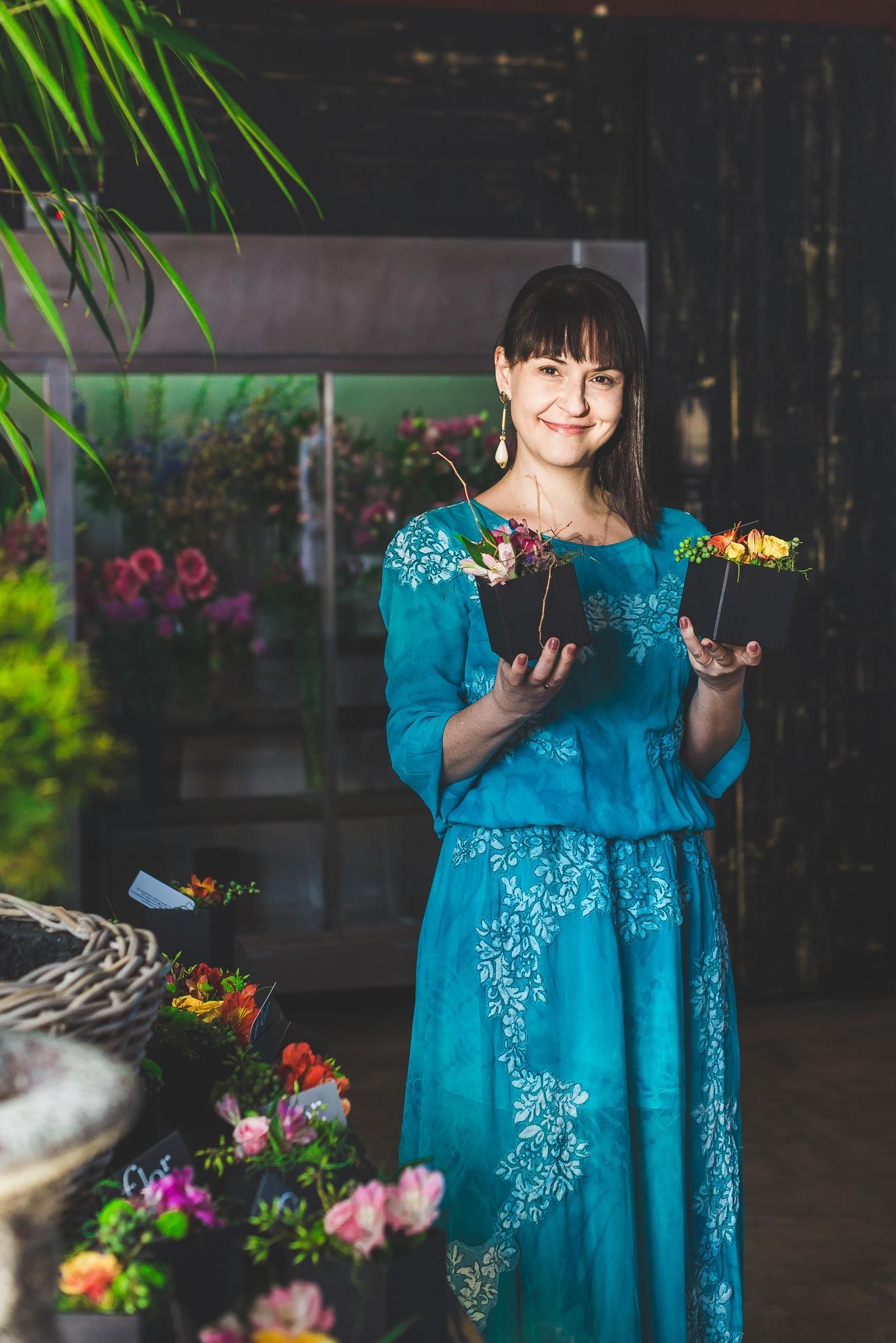 Natália está em pé, com um vestido azul, segurando dois vasos de plantas.