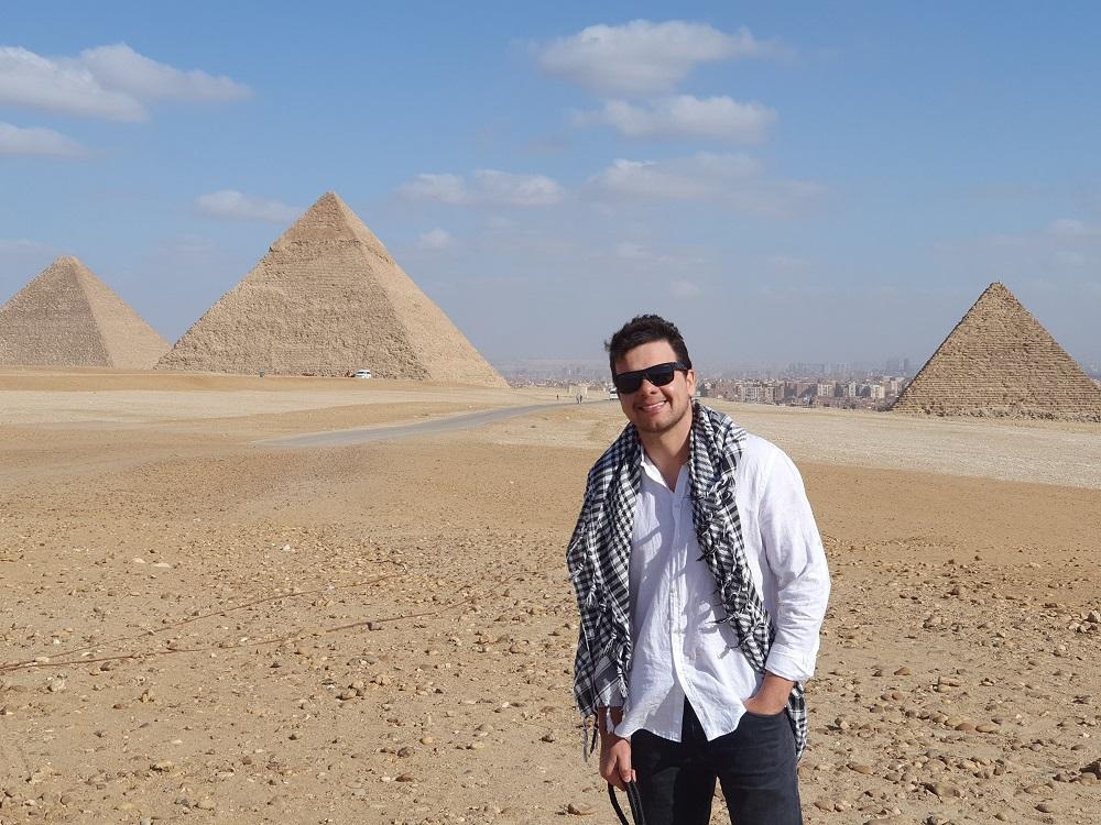 Leandro está de pé em frente às pirâmides do Egito