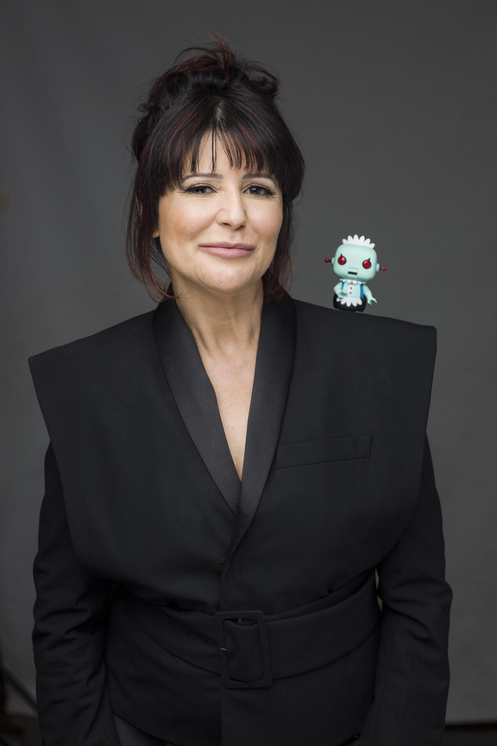 Denise está olhando pra frente com um robozinho no ombro