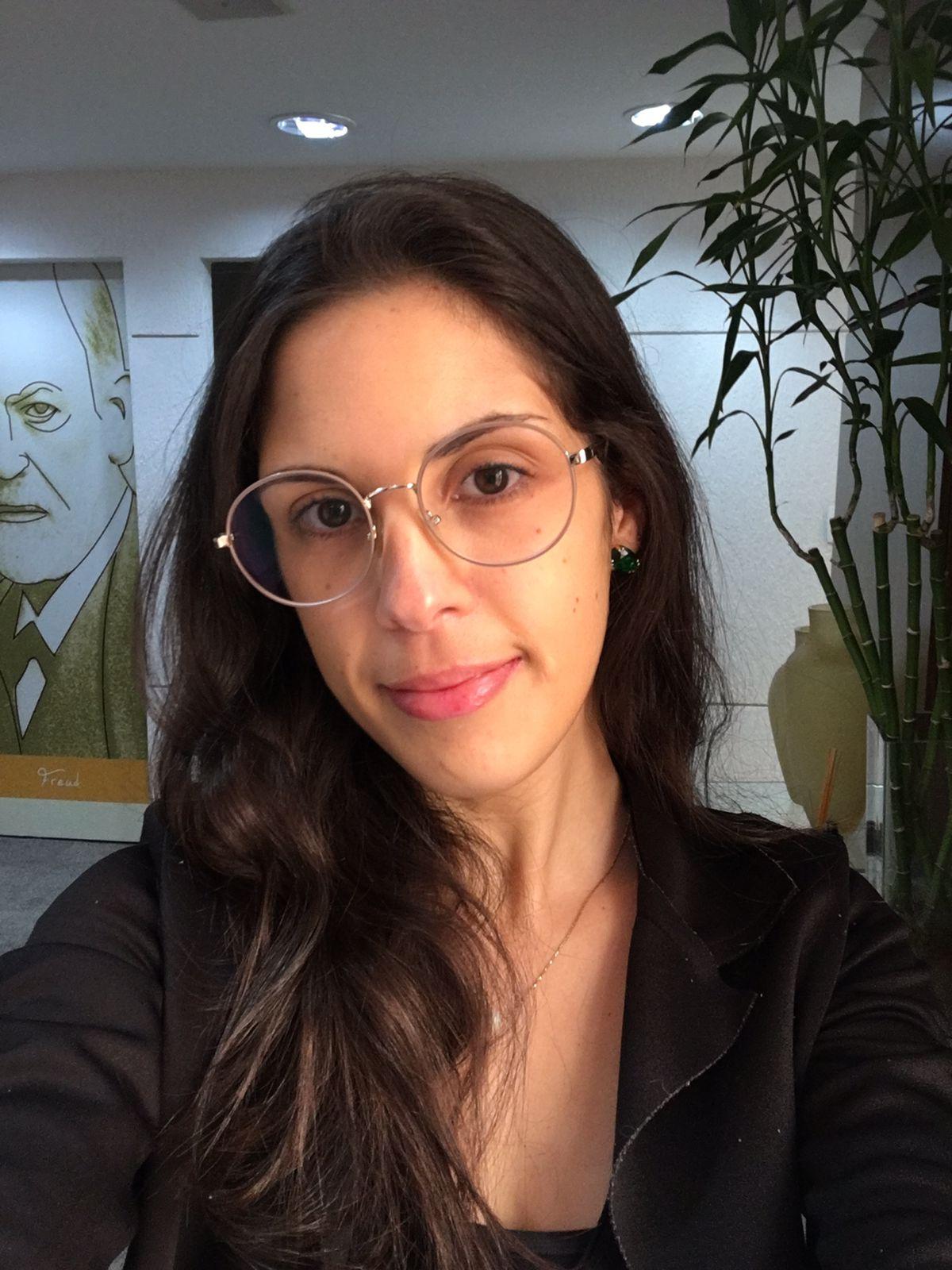 Marilia usa óculos de grau, olha para frente e sorri
