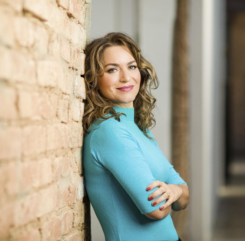 Luciana está encostada na parede, de braços cruzados, olha para frente e sorri